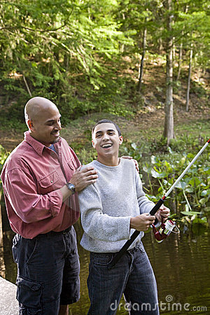 Free Hispanic Teenager And Father Fishing In Pond Stock Photos - 15051383