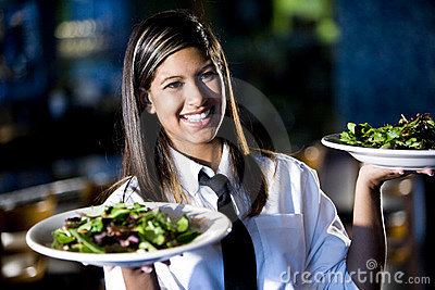 Hispanic waitress in restaurant serving salads