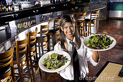 Hispanic waitress serving salads