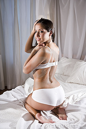 Hispanic woman in bed wearing underwear