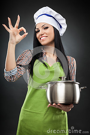 Hispanic woman cook with pot making ok sign
