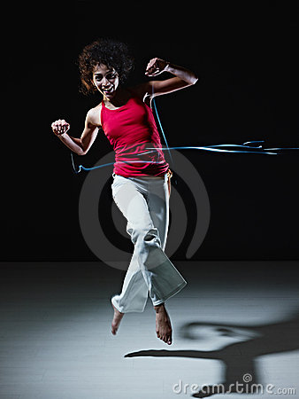 Hispanic woman dancing and jumping with lights