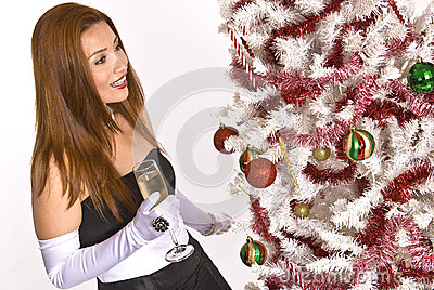 Hispanic woman looking at a decorated Christmas Tree