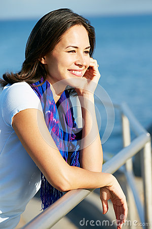 Hispanic Woman Looking Over Railing At Sea