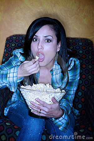 Hispanic woman with popcorn watching television