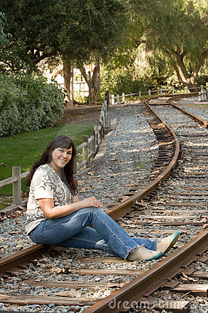 Hispanic woman sits on train tracks