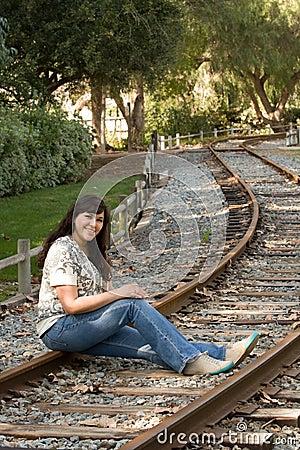 Hispanic woman sits on train tracks