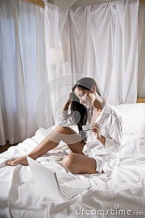 Hispanic woman sitting in bed shopping on internet