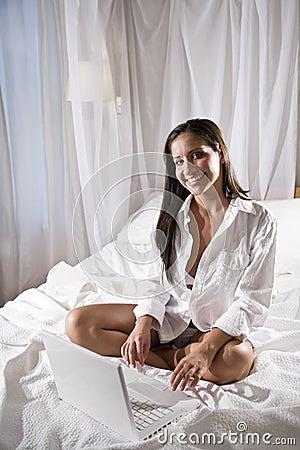 Hispanic woman sitting on bed using laptop