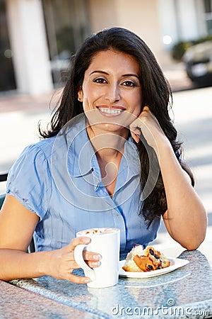 Hispanic woman sitting at sidewalk cafe