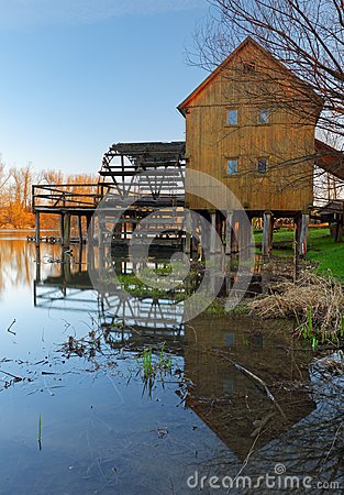 Historic wooden watermill with reflection.