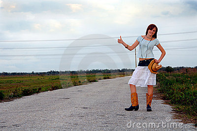 Hitchhiking country girl on rural road