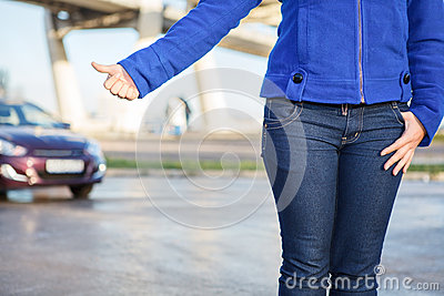 Hitching car with thumb up on roadside
