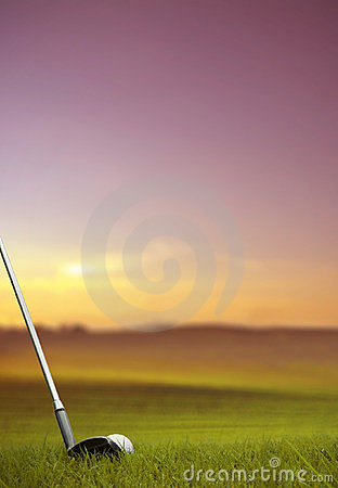 Hitting golf ball along fairway at sunset