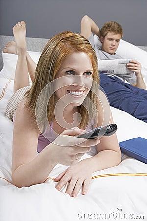 Hållande ögonen på TV för lycklig kvinna i säng