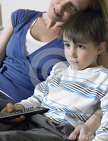 Hållande ögonen på TV för pojke och för moder hemma
