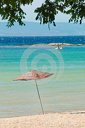 Hölzerner Matten-Regenschirm auf Strand