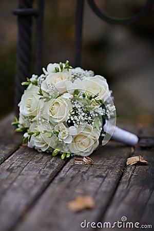 Hochzeits-Ringe und weißer Rosen-Blumenstrauß