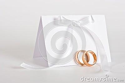Hochzeitsringe und laden mit weißem Bogen ein