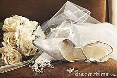 Hochzeitsschuhe mit Blumenstrauß der weißen Rosen und des Ringes
