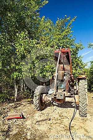 Hogere landbouwer die zijn tractor herstelt