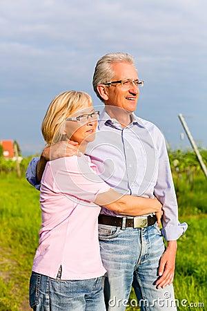 Hogere man en vrouw die hand in hand lopen