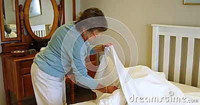 Hogere vrouw die bed in slaapkamer 4k maken stock video