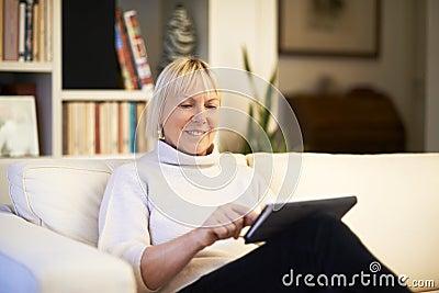 Hogere vrouw die het apparaat van het aanrakingsstootkussen met behulp van