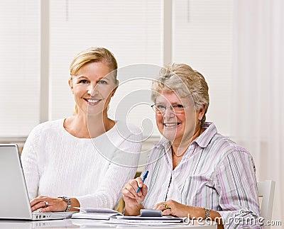 Hogere vrouw het schrijven controles met dochterhulp