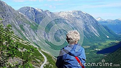 Hogere vrouw op vakantie in bergen Natuurdame geniet van het zicht op een groene vallei en bergen met in Noorwegen stock videobeelden