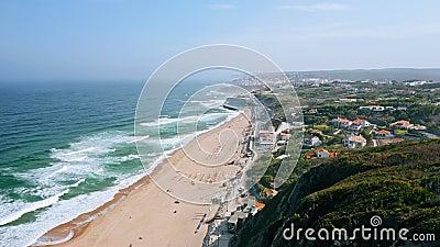 Hohe Luftsicht auf Praia Grande, Sintra Portugal Europa Atlantische Ozeanwellen brechen auf langen touristischen Sandstrand stock footage