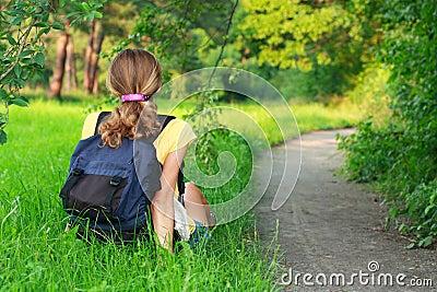 Hojas de ruta (traveler) cansadas de la mujer que se sientan en la hierba