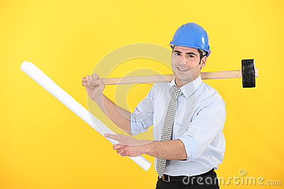 Holding a blueprint and mallet