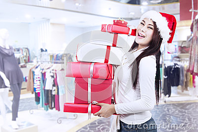 Holding christmas boxes with santa hat at mall