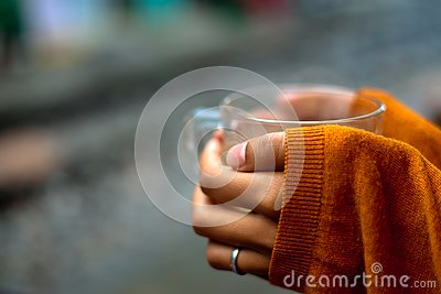 Holding a cup of tea by rails pullover covering hands by half Stock Photo