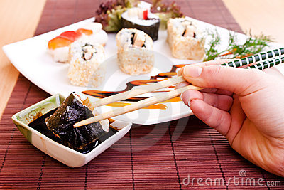 Holding sushi roll with chopsticks