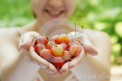 She holds a handful of cherries