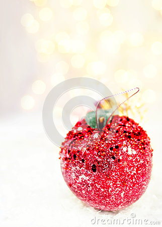 Holiday Apple  bauble on white snow Christmas lights and copy sp