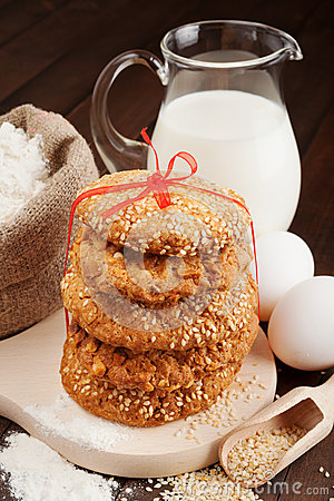 Holiday cookies with red ribbon, flour, milk jug and eggs on kit