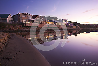 Holiday homes beside a lagoon at sunset