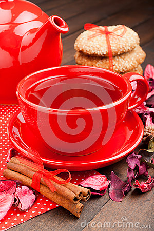 Holiday tea in red cup, cookies, teapot and cinnamon sticks