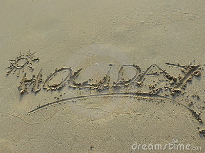 Holiday word written in sand
