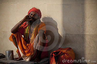 Holy man in orange robes smoking Editorial Stock Photo