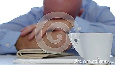 Hombre aburrido y cansado que duerme con un café y un periódico en la tabla metrajes