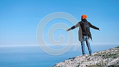 Hombre acertado del ganador del caminante que celebra la victoria que se coloca en el pico del acantilado sobre el mar azul metrajes