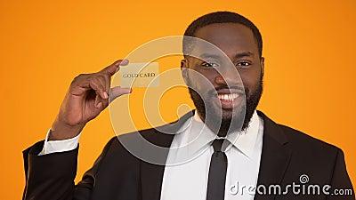 Hombre afroamericano seguro de sí mismo en el traje formal que presenta la publicidad de la tarjeta del oro metrajes