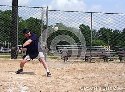 Hombre alrededor para golpear un beísbol con pelota blanda