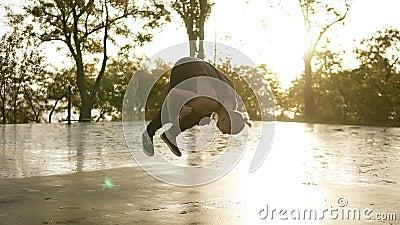 Hombre atlético en la ropa casual negra que realiza los tirones y la voltereta de la acrobacia al aire libre - stedycam a cámara  almacen de metraje de vídeo
