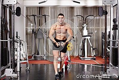 Hombre atlético que tira de pesos pesados