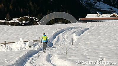 Hombre atleta corriendo en la nieve almacen de metraje de vídeo
